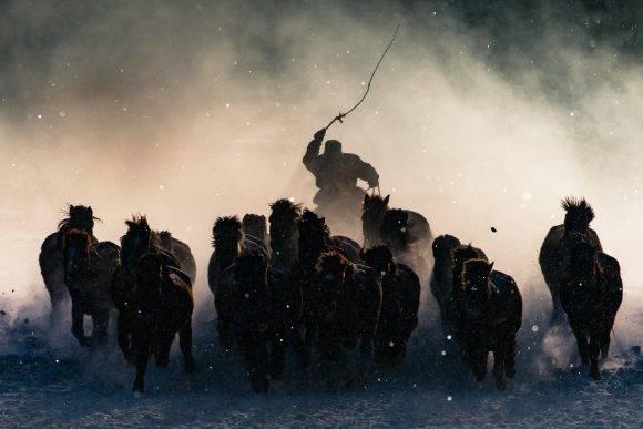 """""""El invierno en la Mongolia Interior es muy severo. A gélidos 20 grados bajo cero y aún menos, con una brisa de nieve constante en todas las direcciones, era bastante difícil convencerme de bajar del auto a tomar fotos. No hasta que vi a los jinetes mongoles alardear de sus habilidades para gobernar a sus corceles a la distancia, rápidamente tomé mi teleobjetivo y capturé el momento en que uno de esos jinetes apareció en medio del rocío de la mañana"""" – Anthony Lau Anthony Lau / National Geographic Travel Photographer of the Year Contest"""