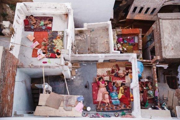 """""""Llegué a mi albergue en Varanasi a las 5:30 AM. Por instinto subí las siete escaleras hasta la terraza (que resultó ser la más alta del vecindario) para ver el amanecer sobre el famoso río Ganges. Con la salida del sol, miré a la derecha de la terraza y quedé boquiabierto. Allí abajo había familias —madres, padres, hijos, hermanos y perros—, todos durmiendo en las terrazas de sus hogares. Era pleno verano en Varanasi y era muy difícil dormir sin aire acondicionado"""". Yasmin Mund / National Geographic Travel Photographer of the Year Contest"""