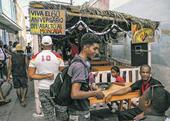Jóvenes caminan junto a un cartel que rememora el asalto al cuartel Moncada, en Santiago de Cuba