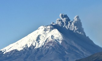 Picture taken from Quito of the Cotopaxi volcano spewing ash on August 18, 2015. Nearly 325,000 people could be affected by an eruption of Cotopaxi, the volcano looming beyond the Ecuadoran capital of Quito, officials said Monday. The biggest risk is from an eruption melting the 5,900-metre (19,000-foot) mountain's snowcap and triggering massive melt-water floods and lahar mudflows that could sweep through nearby towns, Ecuador's minister of risk management Maria del Pilar Cornejo told a press conference. AFP PHOTO / RODRIGO BUENDIA  ECUADOR-COTOPAXI-VOLCANO
