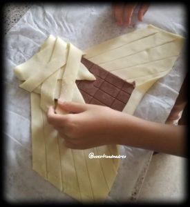 Pasamos las tiras de hojaldre sobre el chocolate para dar forma a la trenza de chocolate