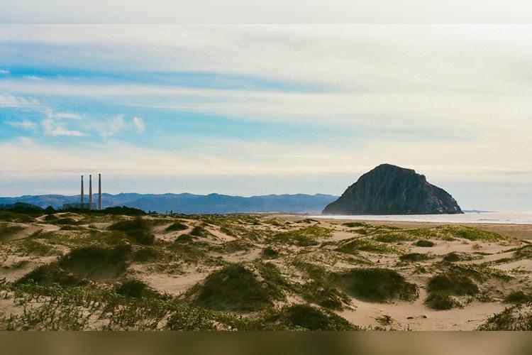 Three smoke stacks and Morro Rock from the dune area on Morro Strand Beach.