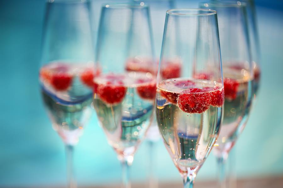 framboisine - Champagne glasses with raspberry. Summer pool party