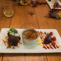 Sugar spun violets, warm gingerbread cake with toffee sauce, yam brûlée, and a chocolate Terrine with papaya and raspberry coulis splashed and fresh berry and sugared mint.
