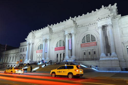 A photograph of the Metropolitan Museum of Art taken at night. The museum is located in New York, NY.