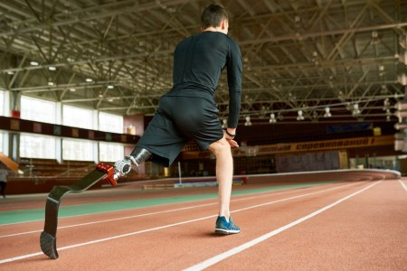 An athletic man with a prosthetic leg getting ready to run track.