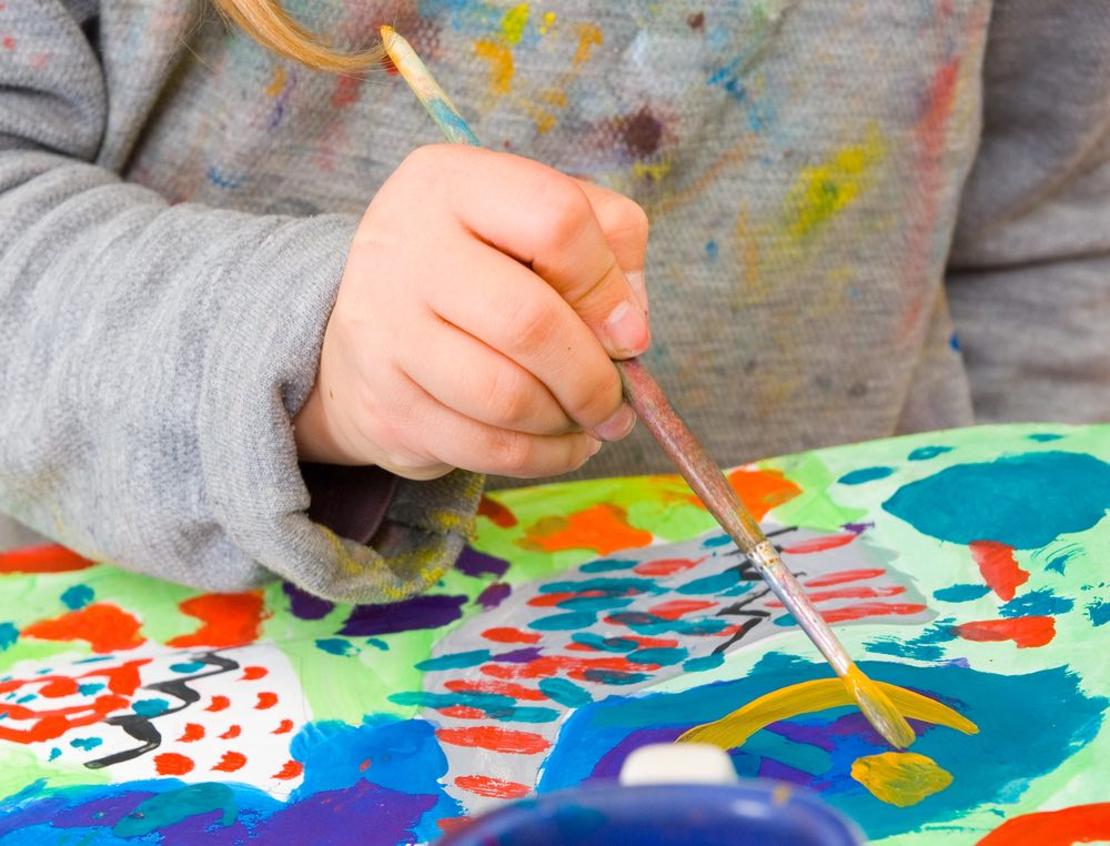 A young student painting with brush