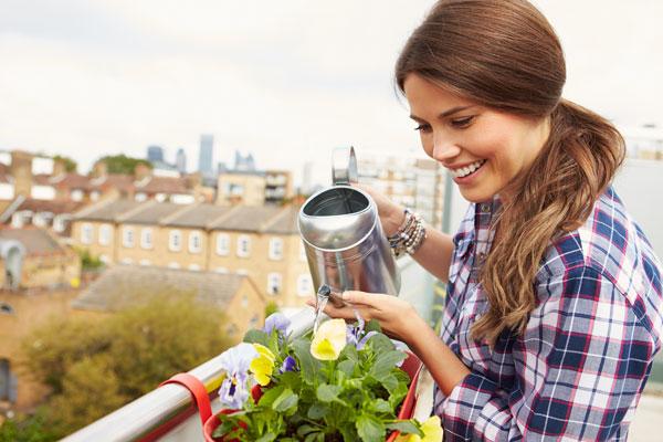 Une femme arrose des plantes sur un balcon