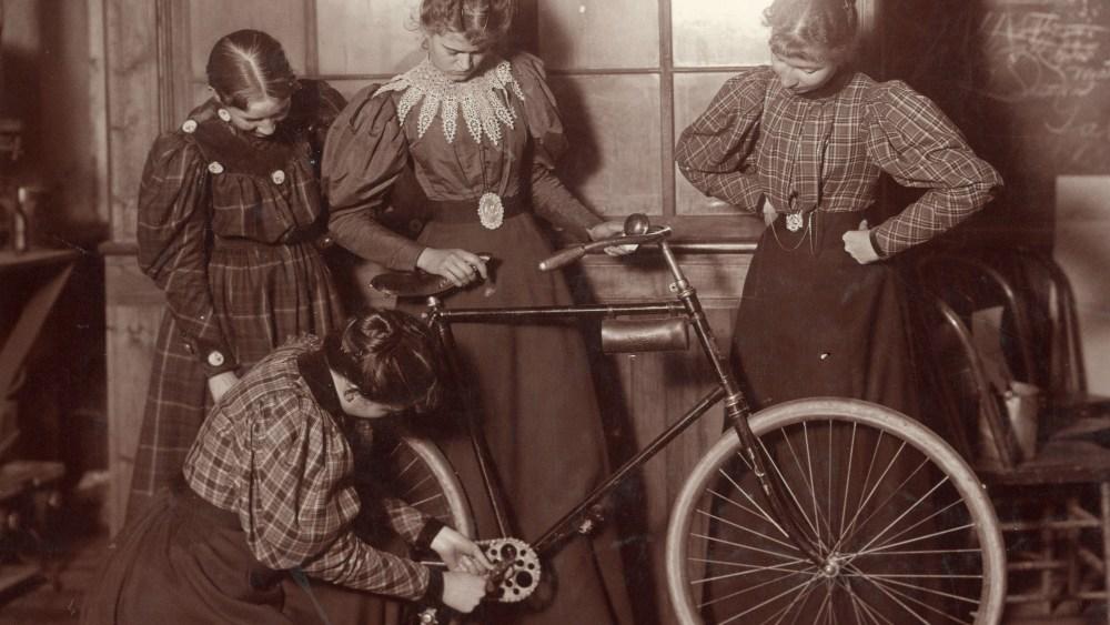 Perempuan sedang memperbaiki sepeda