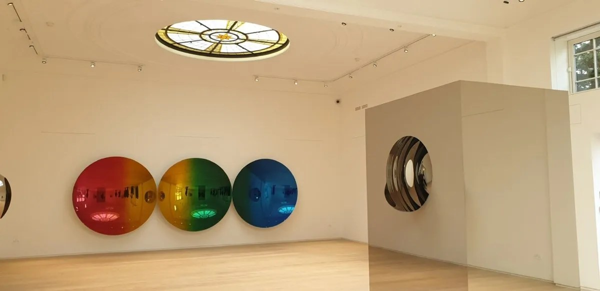 Anish Kapoor reflective artworks hanging beneath an Art Deco ceiling light