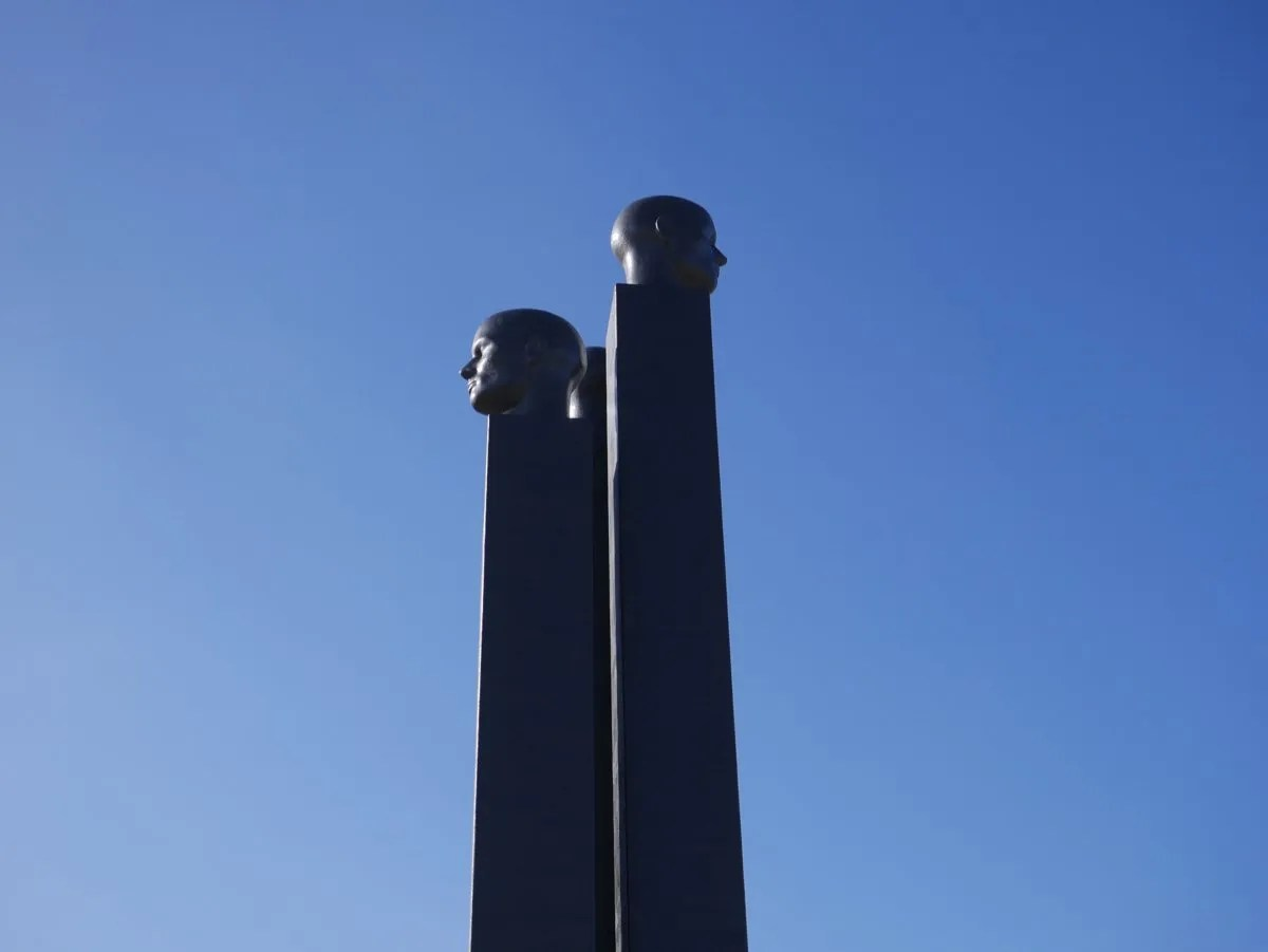 Three Black heads on plinths against blue sky