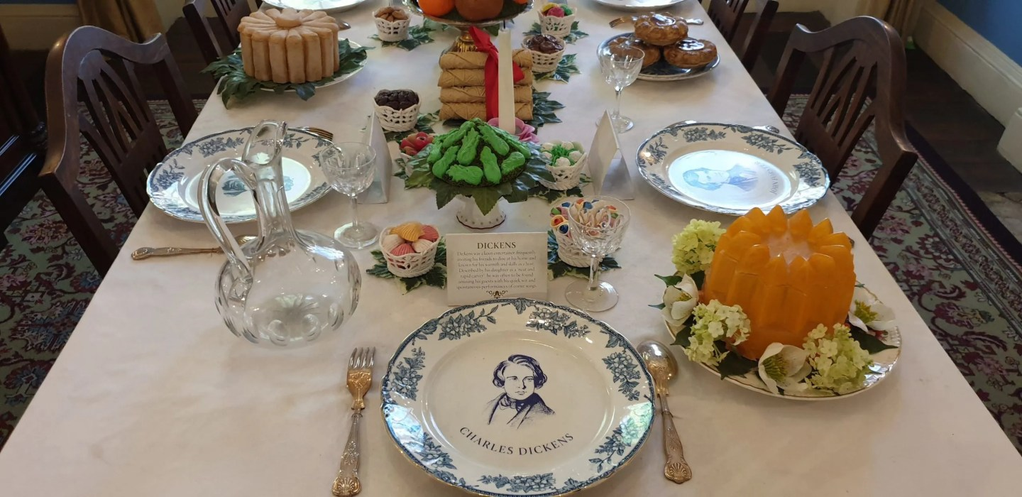 Charles Dickens dinner table set with plates depicting fellow diners