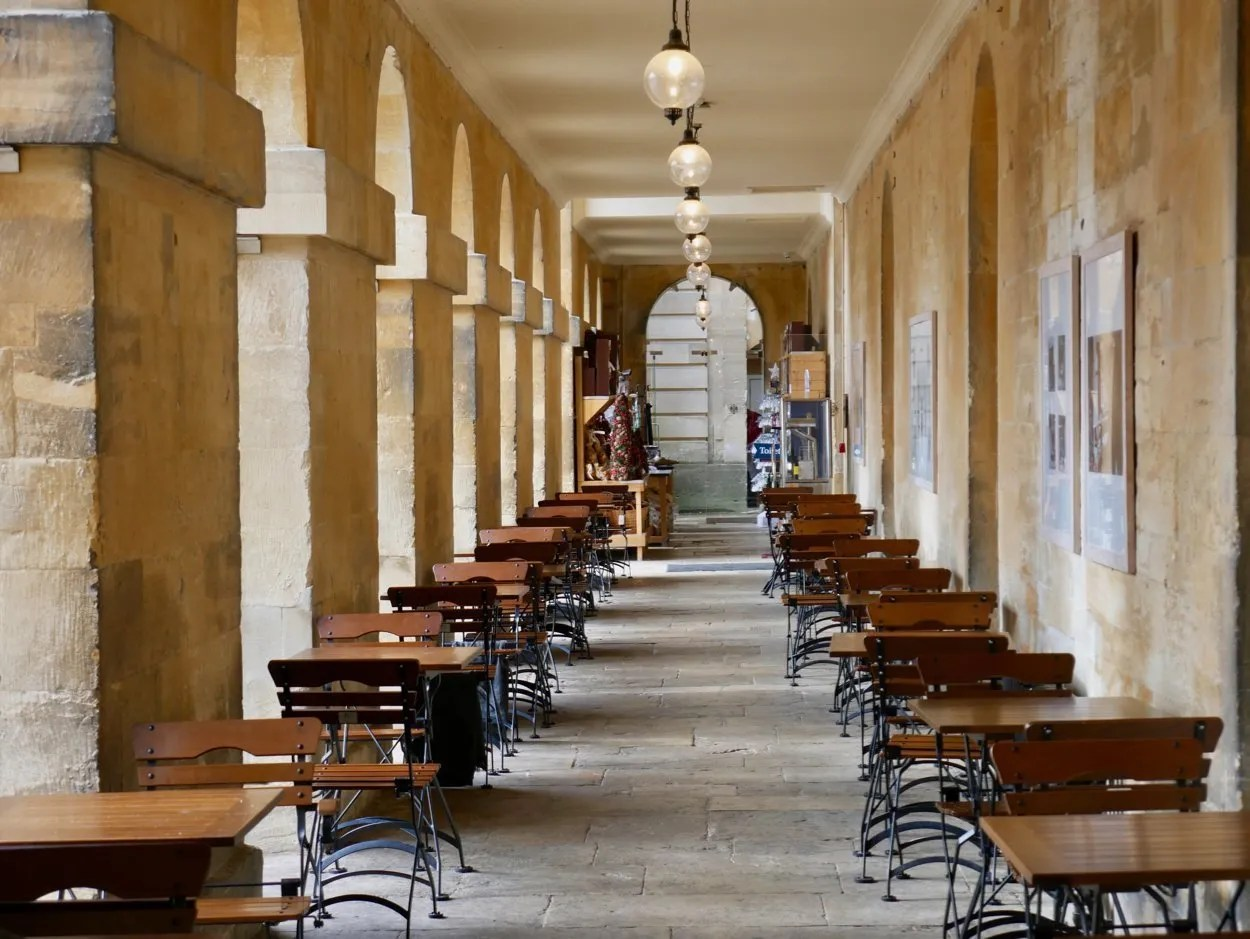 Tables and chairs lining a classical colonnade