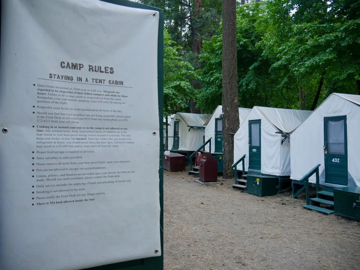 Camp rules text on back on tent cabin door with other curry village tent cabins in background