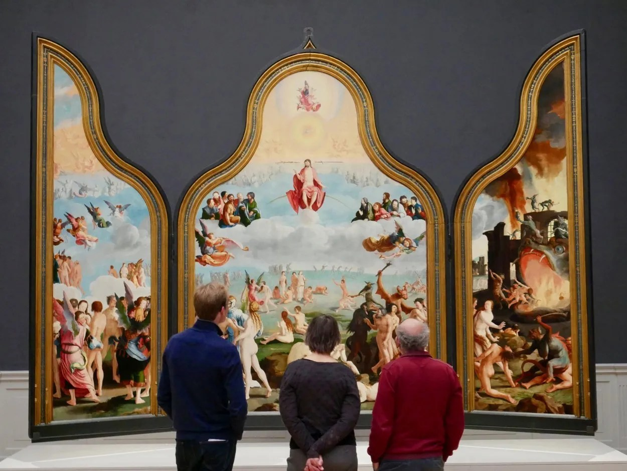 three people standing in front of Last Judgement triptych