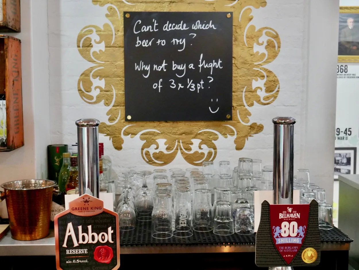Two beer pumps with sign advertising a beer flight