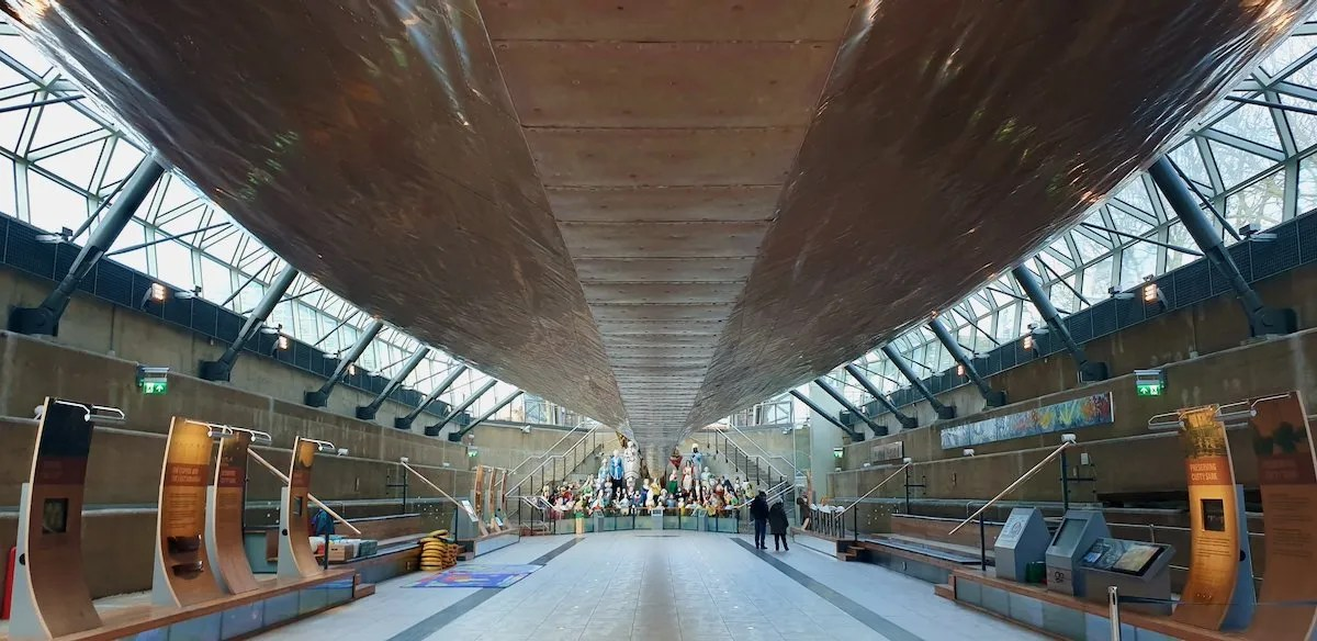 Copper hull of Cutty Sark looking toward collection of ship's figureheads