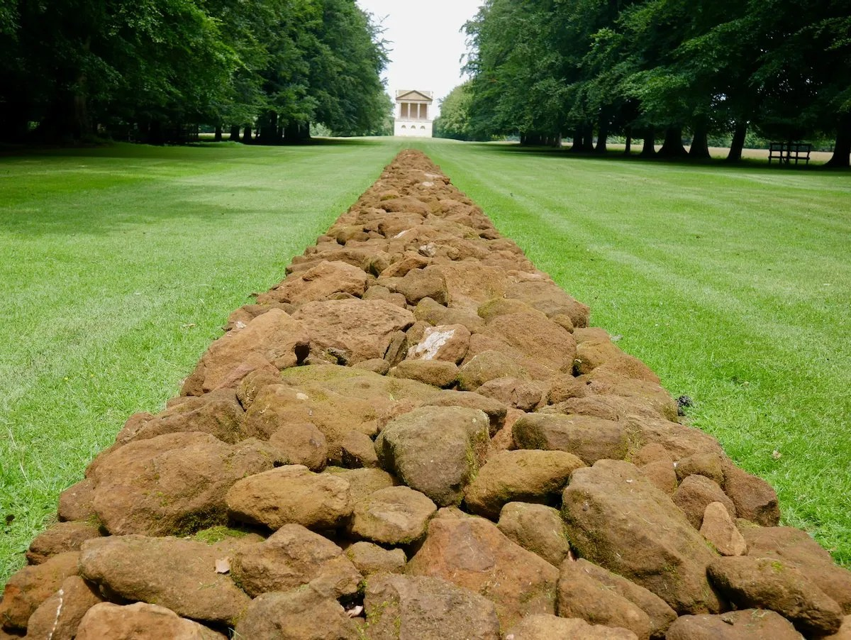 A Line In Norfolk by Richard Long at Houghton Hall a line of sandstone pointing to a Palladian waterpower