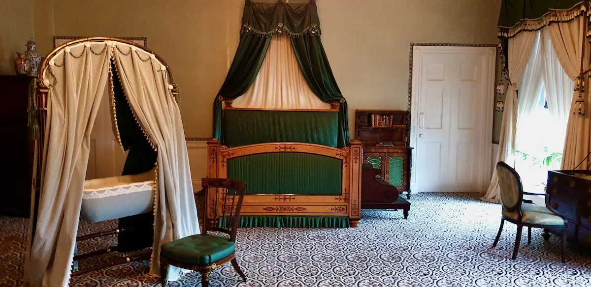 Room where Queen Victoria was born Kensington Palace with green bed and baby crib