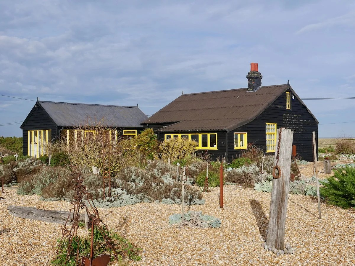Stony garden in front of black cottage with yellow window frames Derek Jarman's Prospect Cottage Dungeness Kent