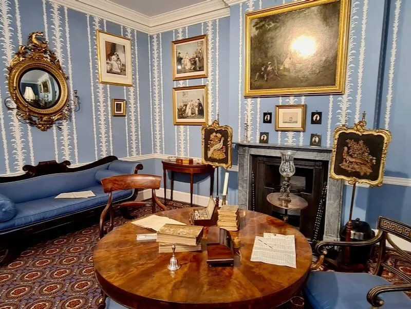 1830s drawing room blue patterned wallpaper, blue sofa and a round wooden table