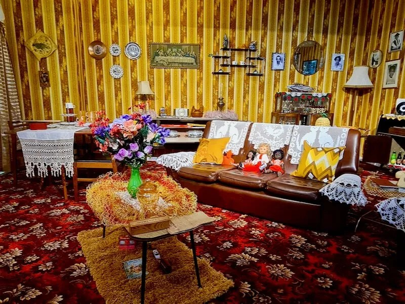 1970s living room brown and yellow wallpaper, brown leather sofa and crocheted doilies