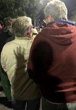 imagen de casal caminhando junto, a sombra de uma mão aparece projetada nas costas da mulher