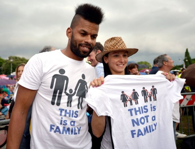 A couple hold-up a  T-shirt with differnt family styles, during a rally in Rome's St John Square on June 20, 2015, during a demonstration against gay unions and the teaching of gender theories in schools, as Prime Minister Matteo Renzi tries to push a civil union bill through parliament. The protest comes as the Italian senate examines a civil union bill, which Renzi wants to see go to a vote in the National Assembly before the summer, with the aim of legislation being enacted by the end of the year.      AFP PHOTO / TIZIANA FABI