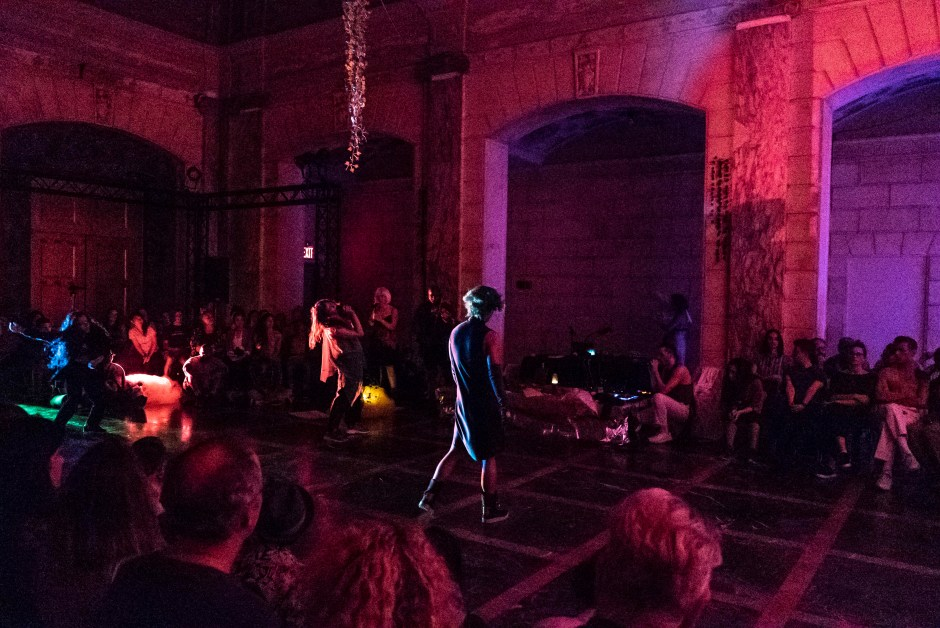alt text: Photo of the performance space in dark red lighting. Audience members sit and stand along the periphery. Ube Halaya, wearing a dress, sneakers, and green wig, stands in the center. anna thompson and taylor knight sing into microphones and Darnell Weaver plays the viola in the background. Samantha Lysaght and Light McAuliffe dance in the center and on the left. Vines hang from the wall and chandelier.