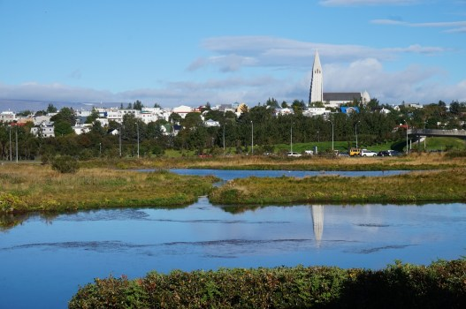 A view of Hallgrimskirkja Church and downtown Reykjavík from across the Tjörnin lake