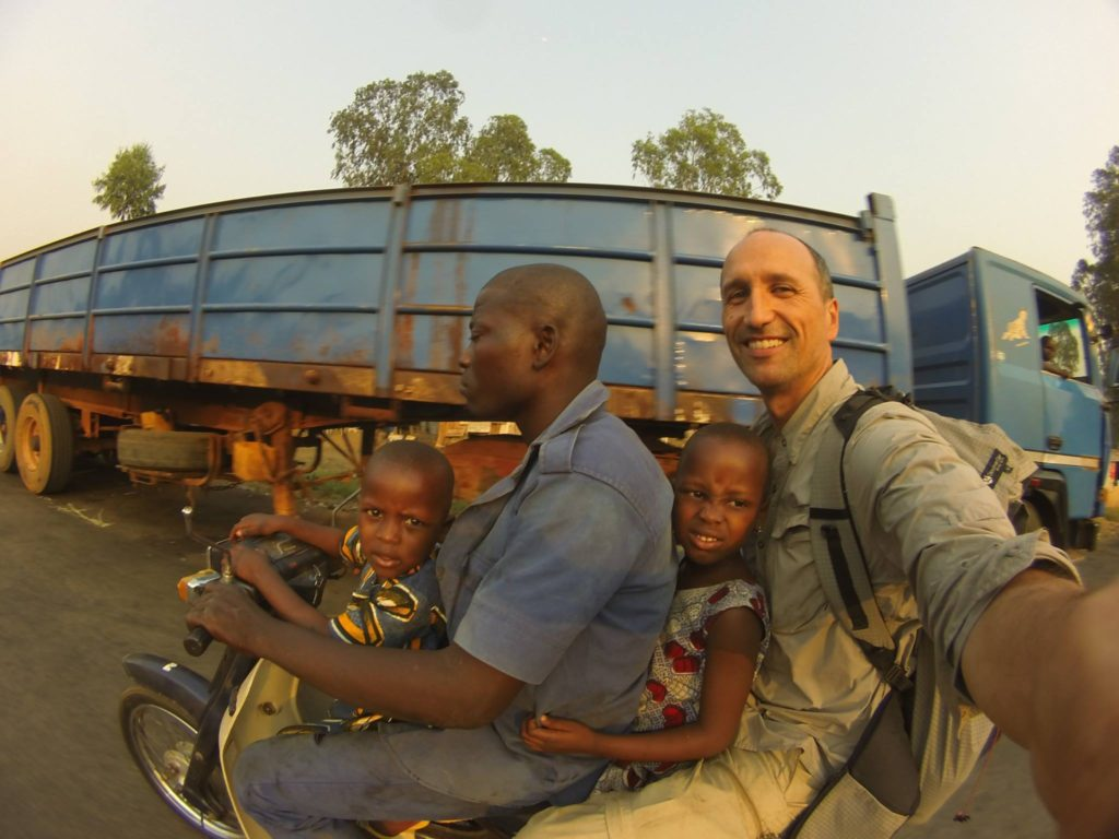 Storyteller Francis Tapon riding on a scooter in Africa