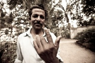 7. After voting, man displays his finger marked with indelible ink