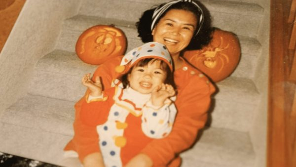 A baby picture shows a toddler dressed for Halloween in her mom's arms.