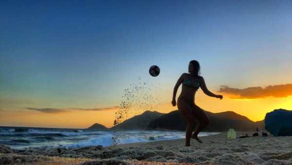 Yuujou finalist, Renata, plays soccer on the beach.