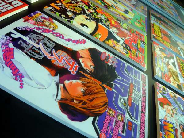 Diagonally-angled photo taken of Shonen Jump issue covers. Each cover has art of various characters from popular Japanese manga characters/series.