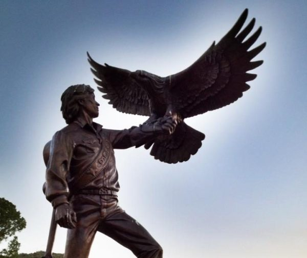 stature of John Denver with an eagle on his arm