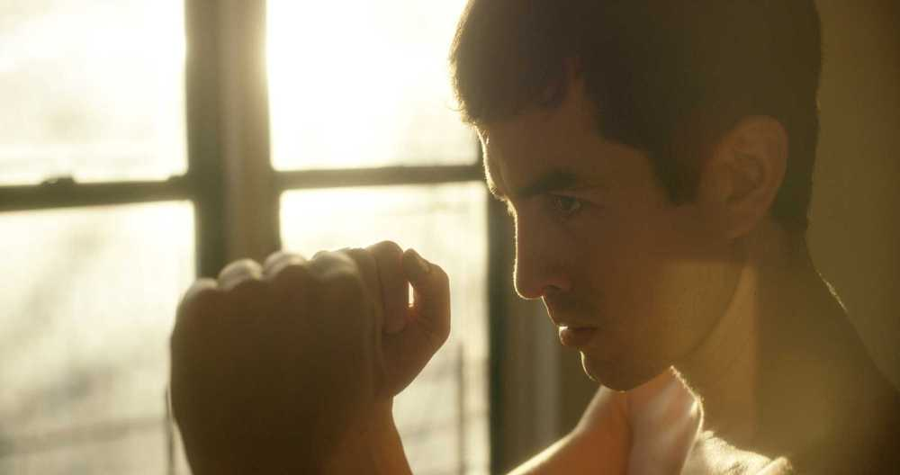 Transgender immigrant-focused Close up of young man fists up boxing stance in natural sunlight.