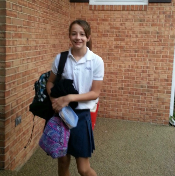 Military BRAT, Brynne Adams smiling on her first day of sixth grade. She has her backpack over one shoulder and is holding a purple and blue lunch box. Adams is wearing a white collar shirt and a dark pleated skirt.
