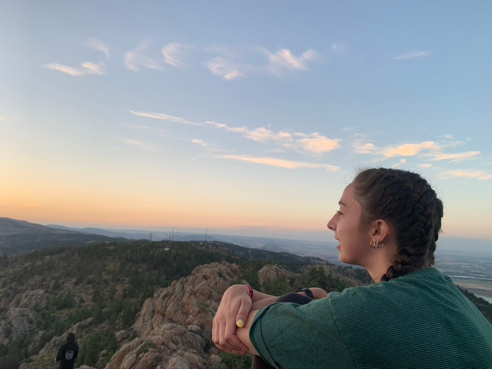 Adams wearing green and white stripped shirt, hoop earrings and two braids as she looks into the distance atop of Horsetooth Rock.