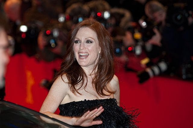 Actress Julianne Moore at a red carpet during a movie premiere, she is wearing in black strapless dress, smiling.