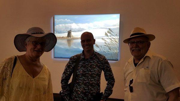 Marc Rieu, Marianne Visser van Klaarwater en Peter Lasschuit voor Marcs werk ''Molen in KInderdijk'' tijdens zijn expositie in Theater aan het Vrijthof Maastricht