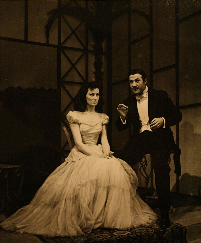 """<p>1954-1955 sezonunda sanatseverlerle buluşan ve Kenter'in (solda) başrollerini usta oyuncu Cüneyt Gökçer (sağda) ile paylaştığı Jean Anouilh'ın """"Şatoya Davet"""" oyunundan bir fotoğraf da tiyatronun ilk yıllarına ışık tutuyor.<br></p>"""