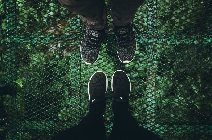 looking down at feet on mistico hanging bridges - famous landmarks in costa rica