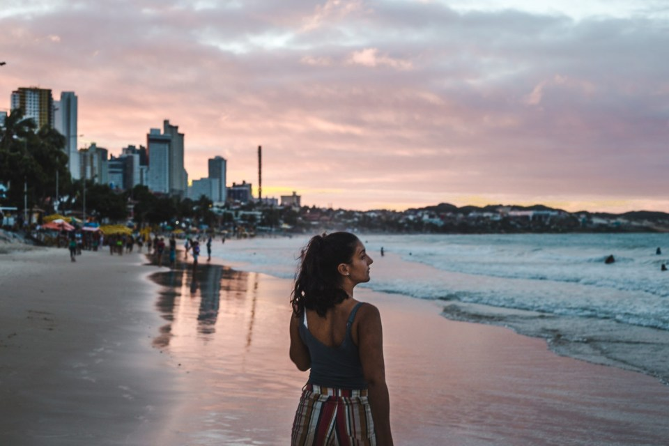 backpacker girl on beach in brazil at sunset: why it's great for having travel on your résumé