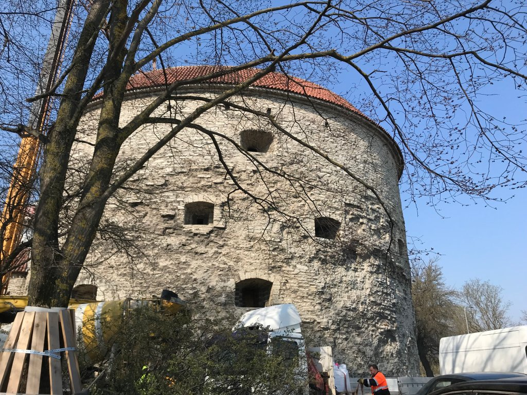 Photograph of Fat Margaret's Tower, Tallinn, Estonia. A very large cylindrical tower made from limestone, with several recesses punched out for cannons.