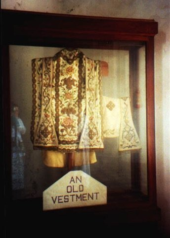 "A wooden museum cabinet containing ecclesiastical robes. A sign reads ""An old vestment""."