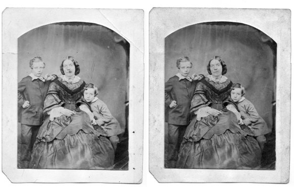 Two black and white Victorian photographs side by side. The left hand photo features a lady sat in the middle with a boy on each side (her sons). The photo has scratches and dots on it. The right hand photo, of the same scene, has had the scratches and dots removed digitally and is much clearer.