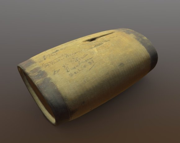 3D scan of a small wooden water canteen from 1875. It is oval in shape, with a hole on the top and darker bands at each end.