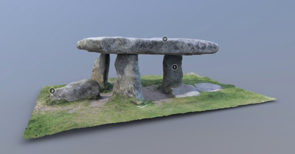 Screenshot of a 3D model of Lanyon Quoit. Three upright stones on a rectangular bed of grass support a huge granite capstone. Three white numbers are visible on black backgrounds attached to several parts of the quoit. These can be clicked to read more information.