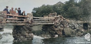 A group of people standing on a stone and wood bridge